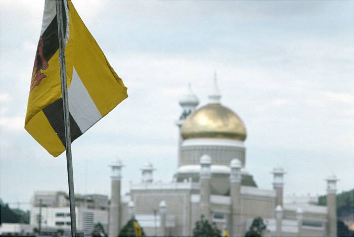 Brunei Flag, Sultan Omar Ali Saifuddin Mosque in the background. Bandar Seri Begawan